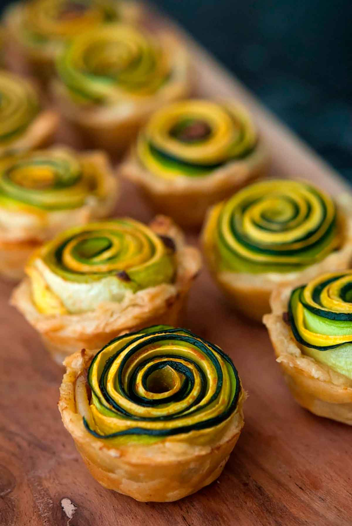 8 squash rosettes on a wooden tray.