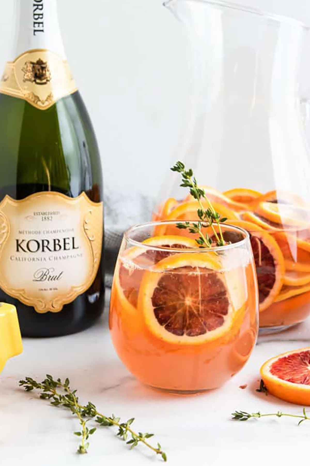 A cocktail filled with oranges and thyme beside a bottle of champagne on a marble table.