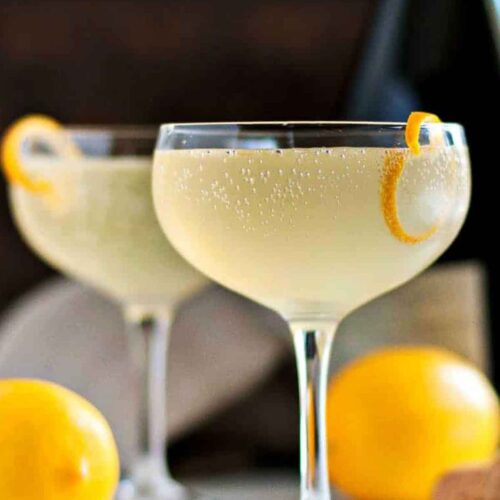 2 French 75 cocktails garnished with lemon on a table beside 2 lemons and a bottle in the background.