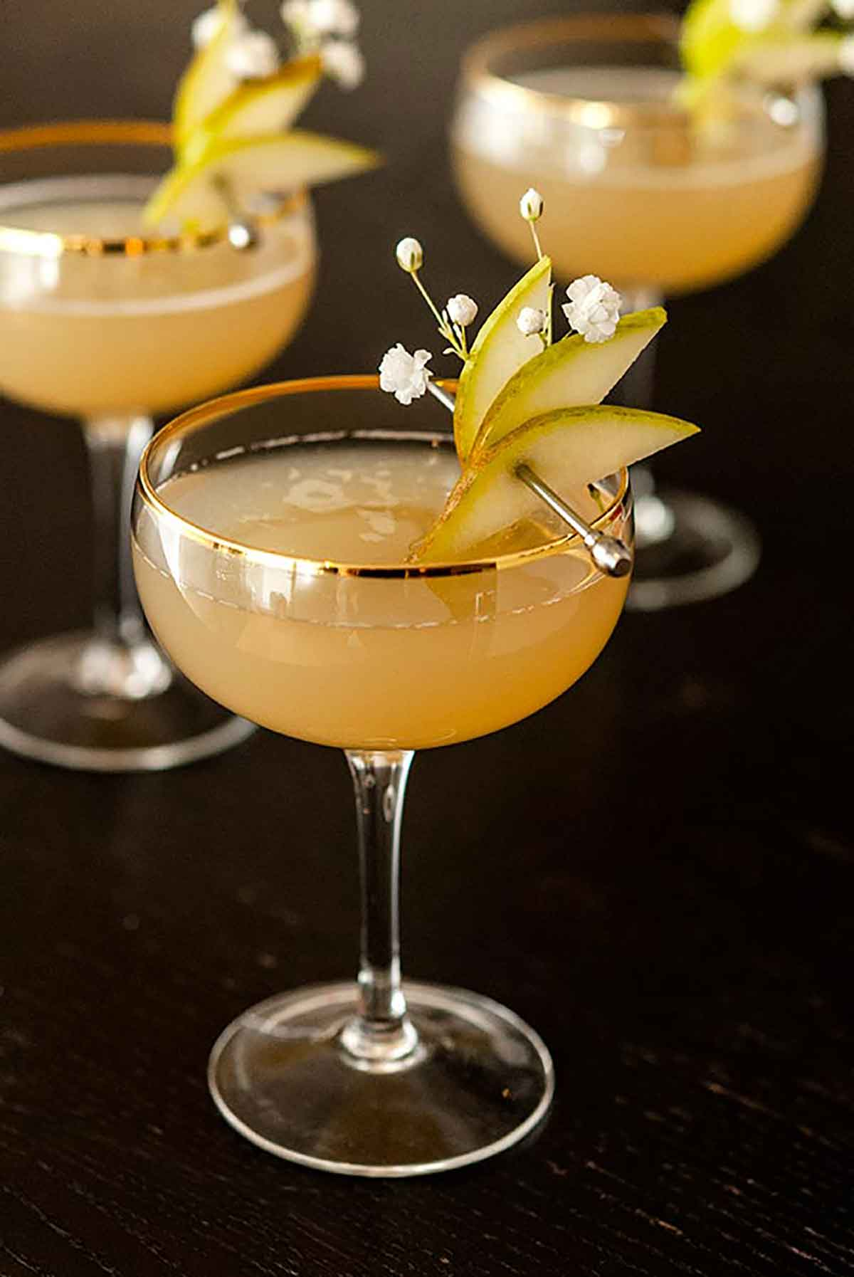 3 pear and ginger cocktails, garnished with sliced pears on a cocktail pin and a few baby's breath flowers.