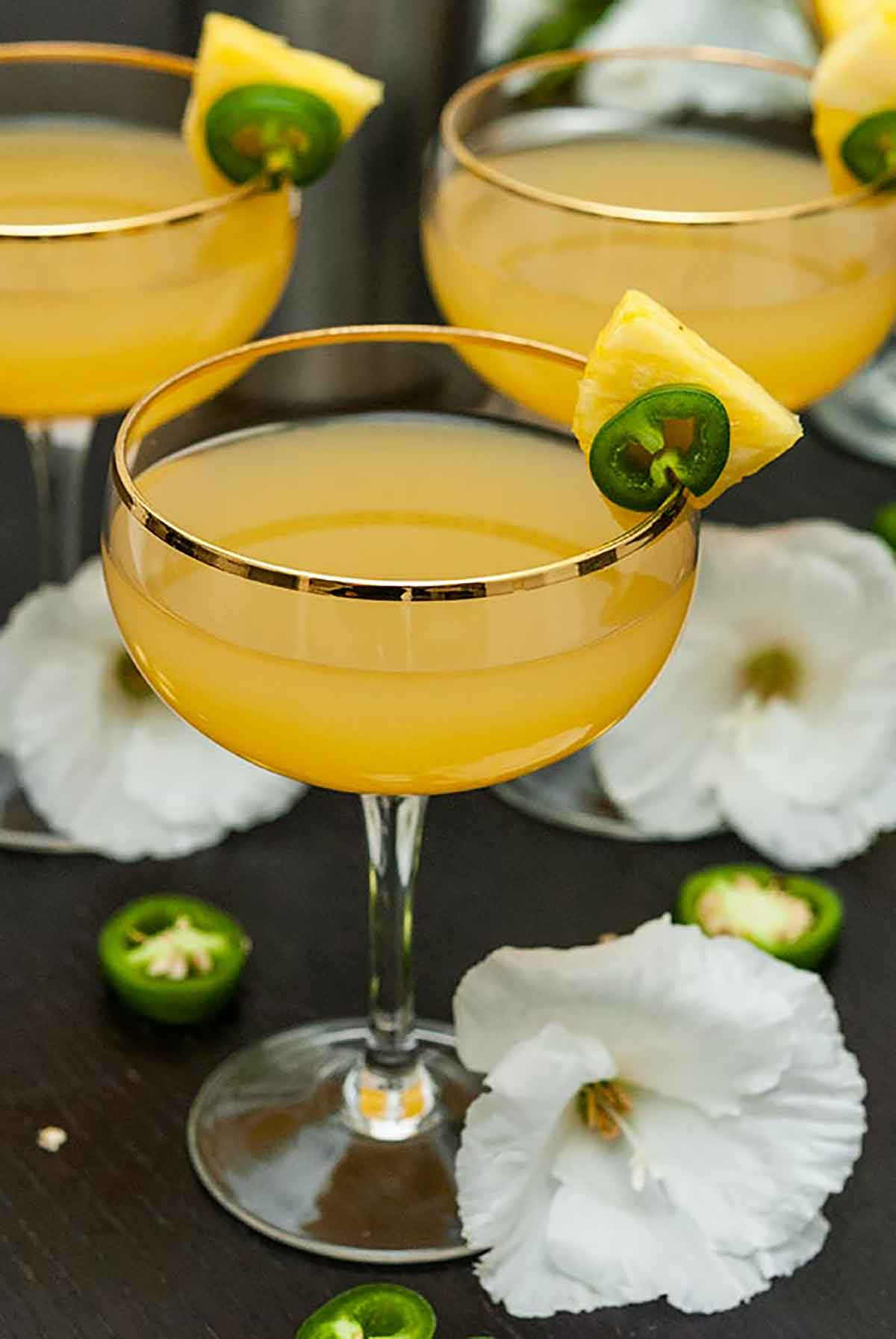 3 pineapple cocktails on a table, garnished with pineapple and jalapeños, surrounded by tropical flowers.