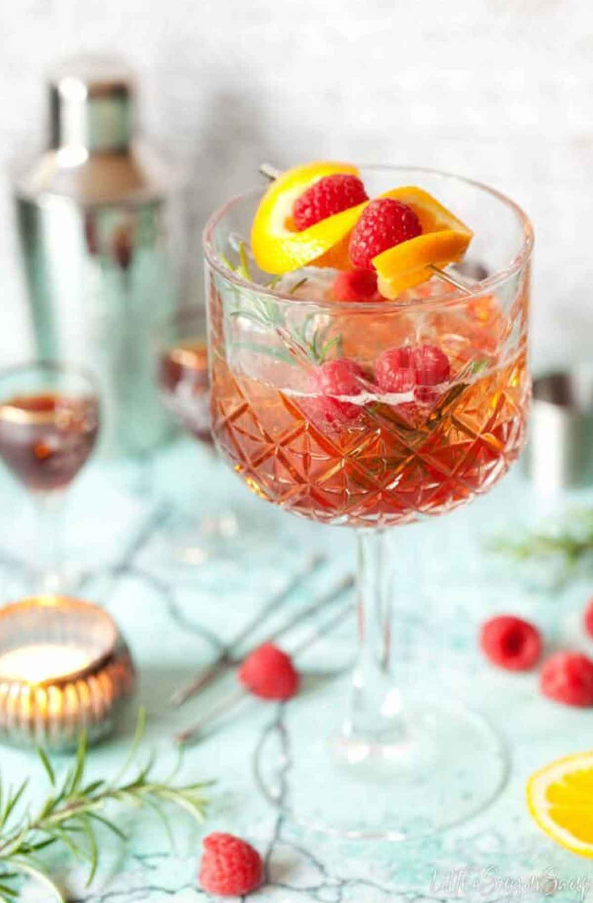 A cocktail on a table, sprinkled with raspberries, garnished with lemon and raspberries.