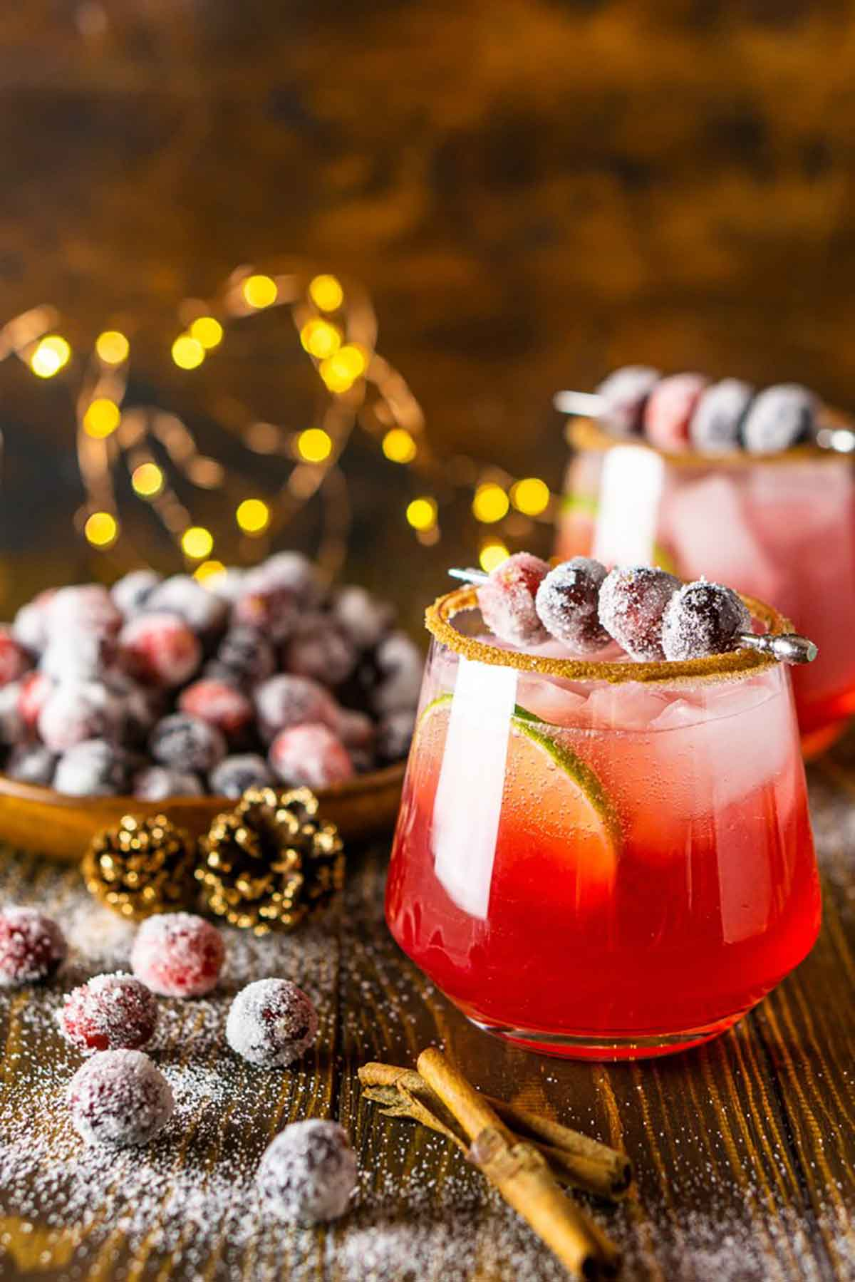 2 cocktails on a table with sugared cranberries and cinnamon sticks.