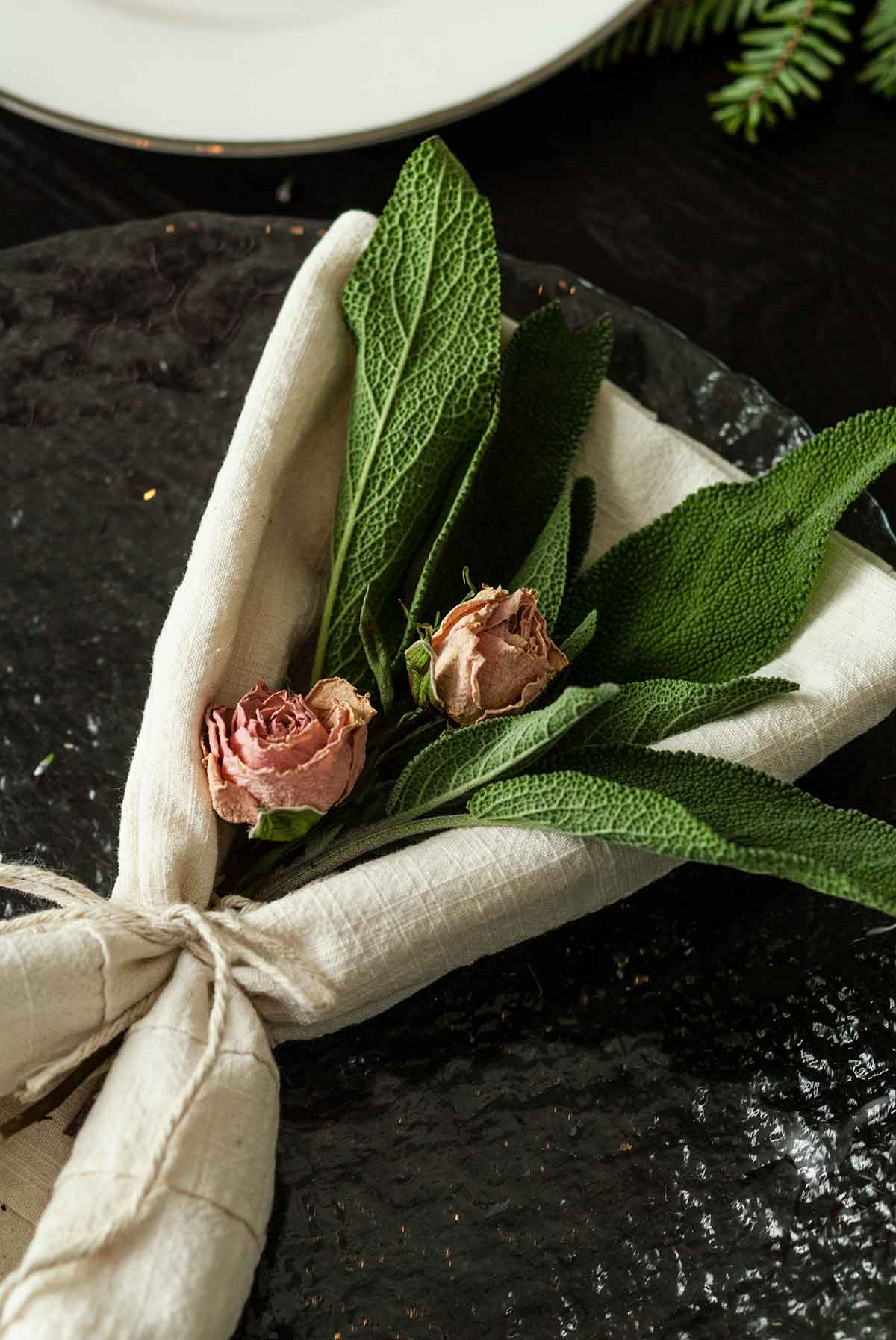 2 small roses and a few leaves of sage in a napkin tied with string, on a plate.