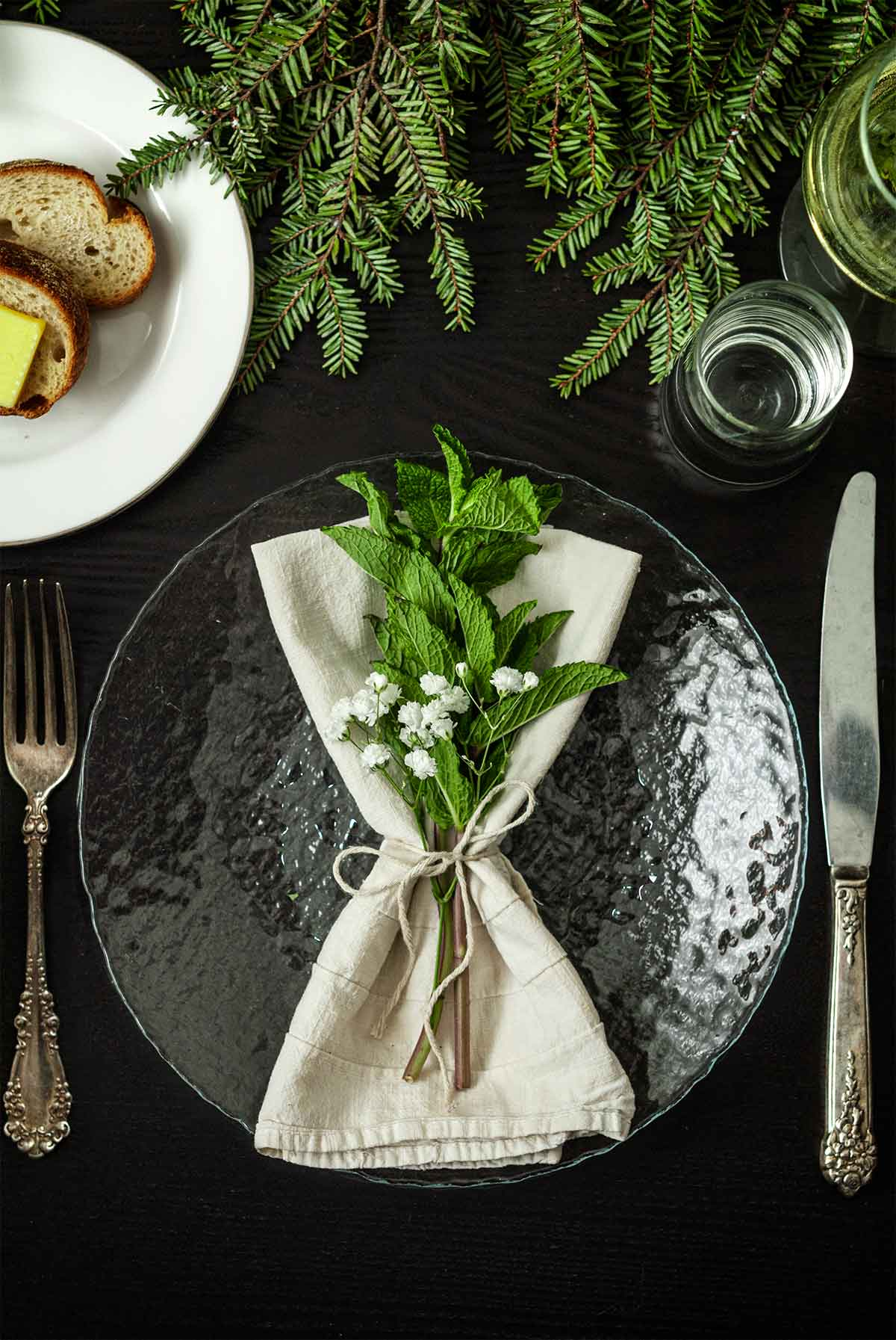 Mint and Baby's Breath in a napkin on a plate on a table with holiday greenery, a plate of bread, silverware and glassware.