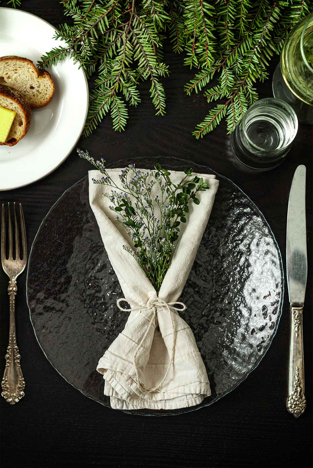 Caspia and Thyme in a napkin on a plate on a table with holiday greenery, a plate of bread, silverware and glassware.