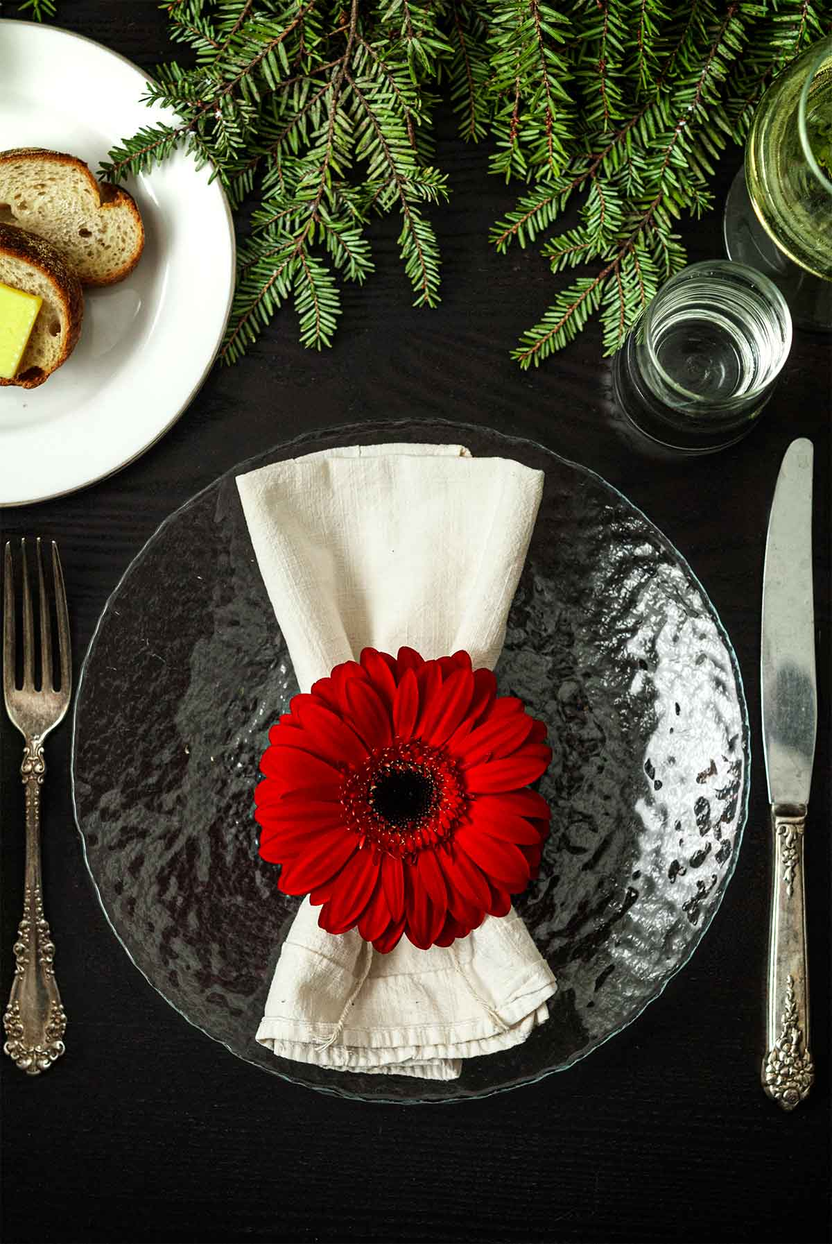 A Gerbera Daisy on top of a napkin on a plate on a table with holiday greenery, a plate of bread, silverware and glassware.