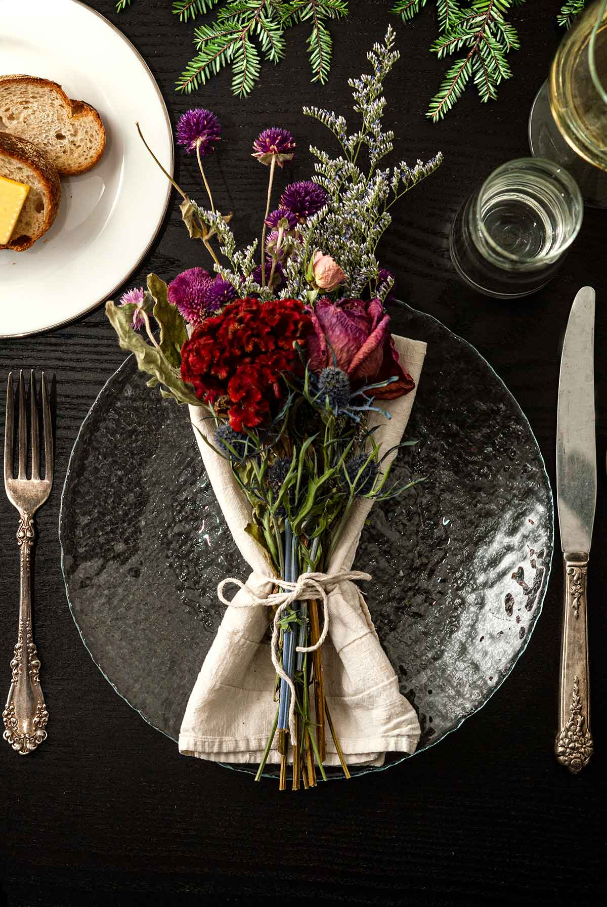 A bouquet of flowers in a napkin on a plate on a table with holiday greenery, a plate of bread, silverware and glassware.
