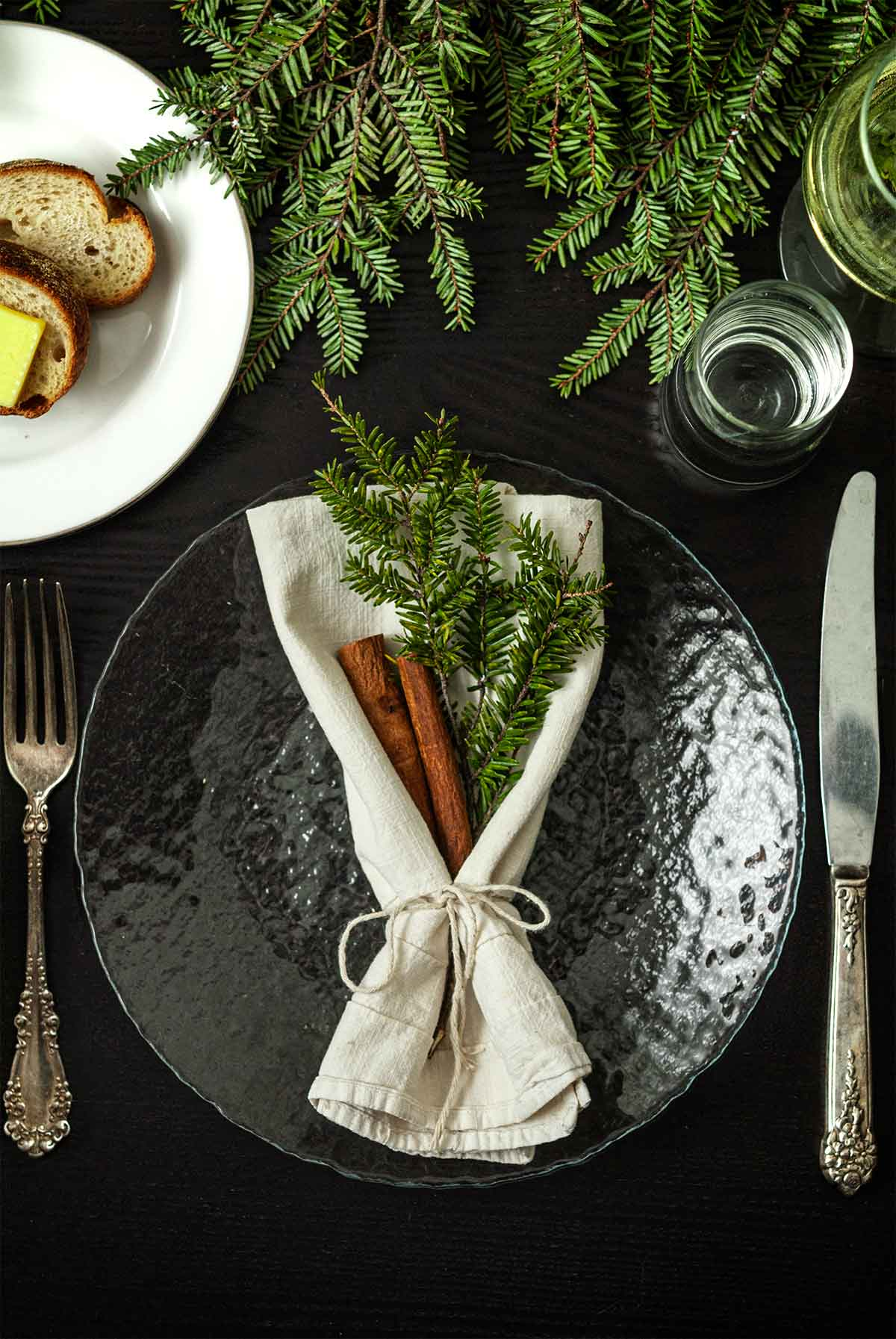 Sprigs of pine and cinnamon sticks in a napkin on a plate on a table with greenery, a plate of bread, silverware and glasses.