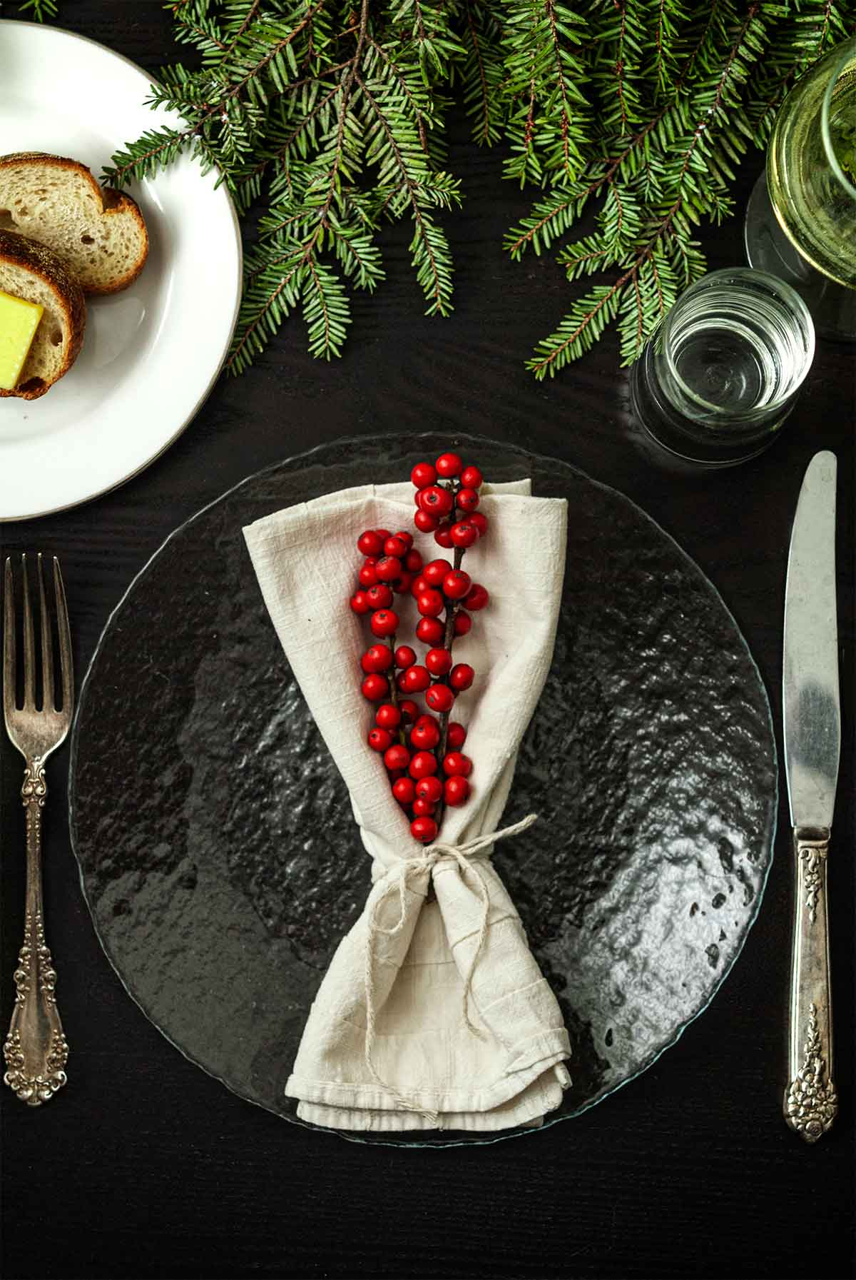 2 sticks of Ilex in a tied napkin on a plate on a table with holiday greenery, a plate of bread, silverware and glassware.