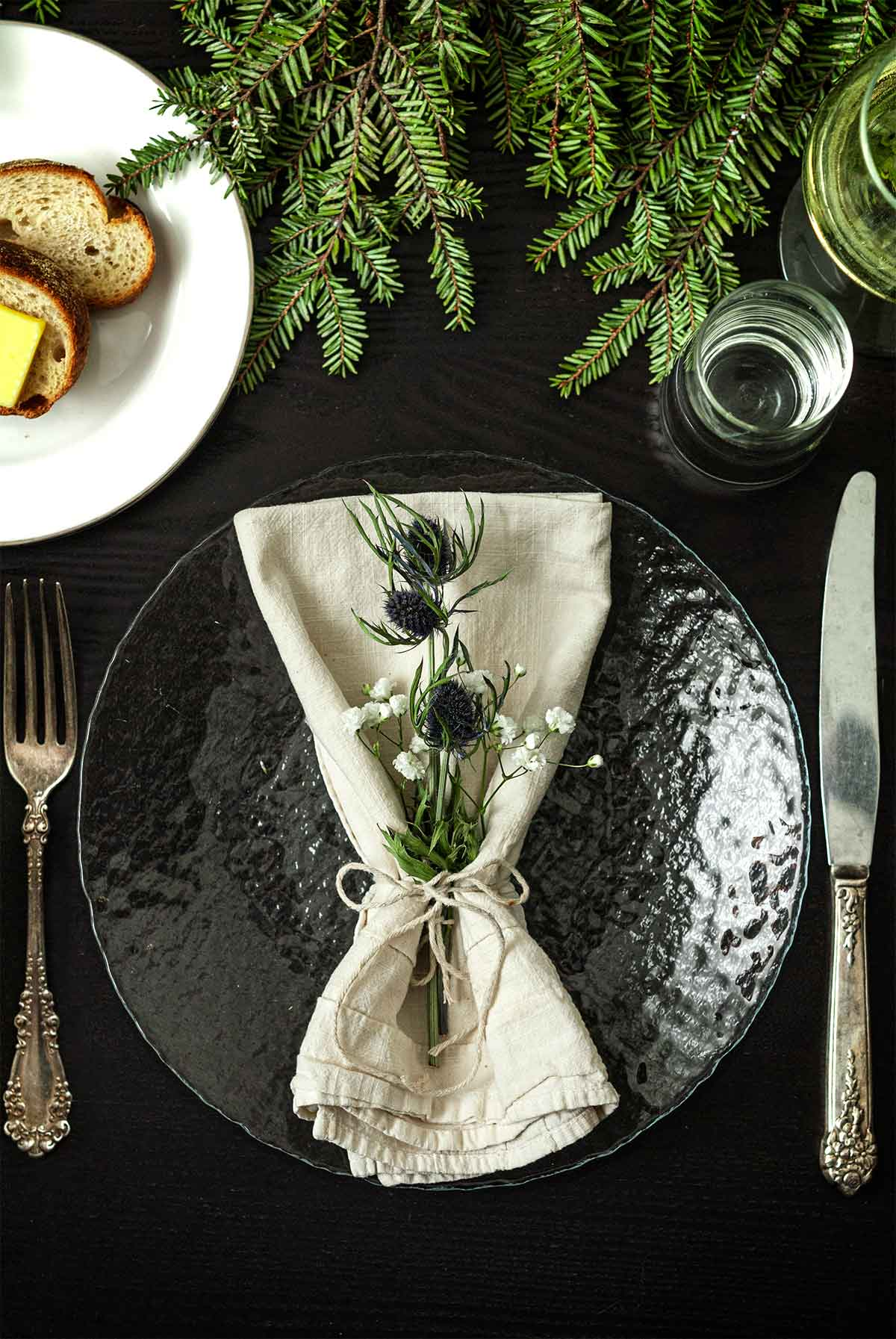 Thistle and Baby's Breath in a napkin on a plate on a table with greenery, a plate of bread, silverware and glassware.