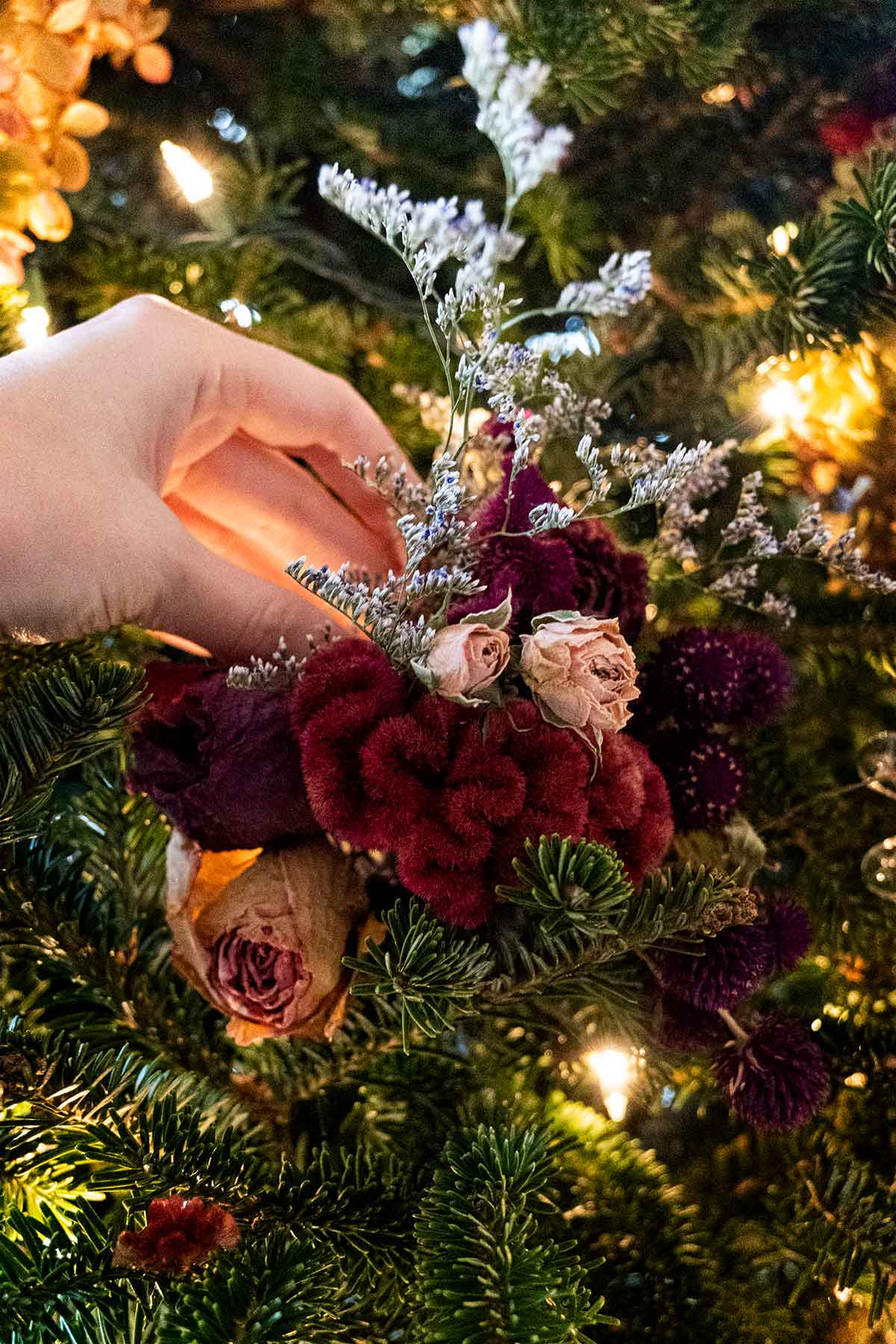 A hand placing a flower bouquet on a Christmas tree.