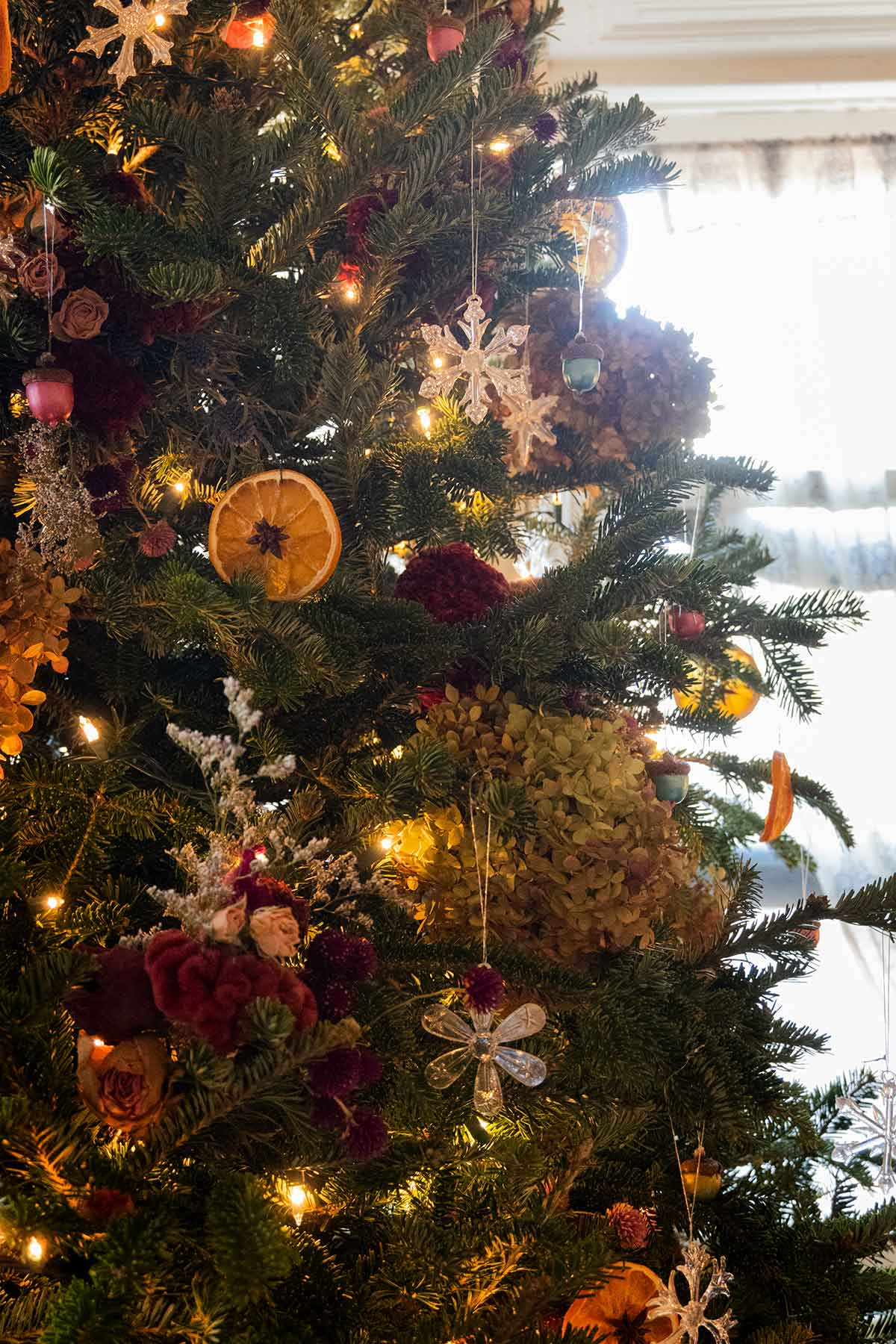 A Christmas tree in front of a bright window, decorated with flowers, orange slices and other bright ornaments.