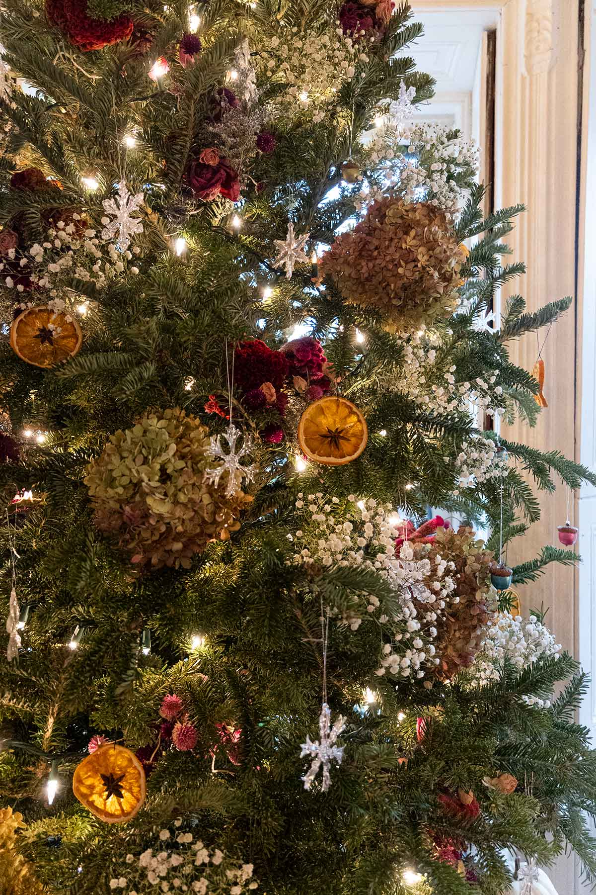 A Christmas tree with baby's breath and flower decorations, dry oranges and glass snowflakes..