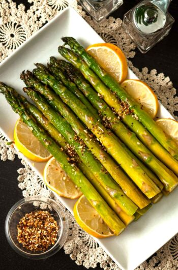 A stack of lemon asparagus on a plate, garnish with lemons.