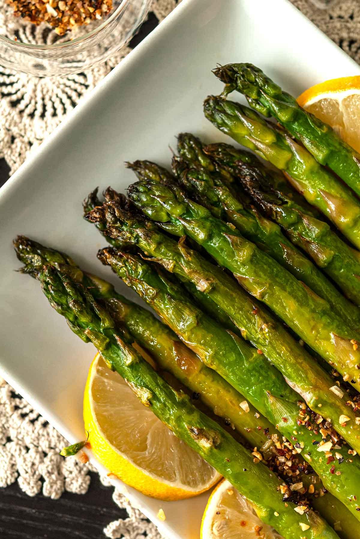 Crispy asparagus tips on a plate, garnished with lemons.