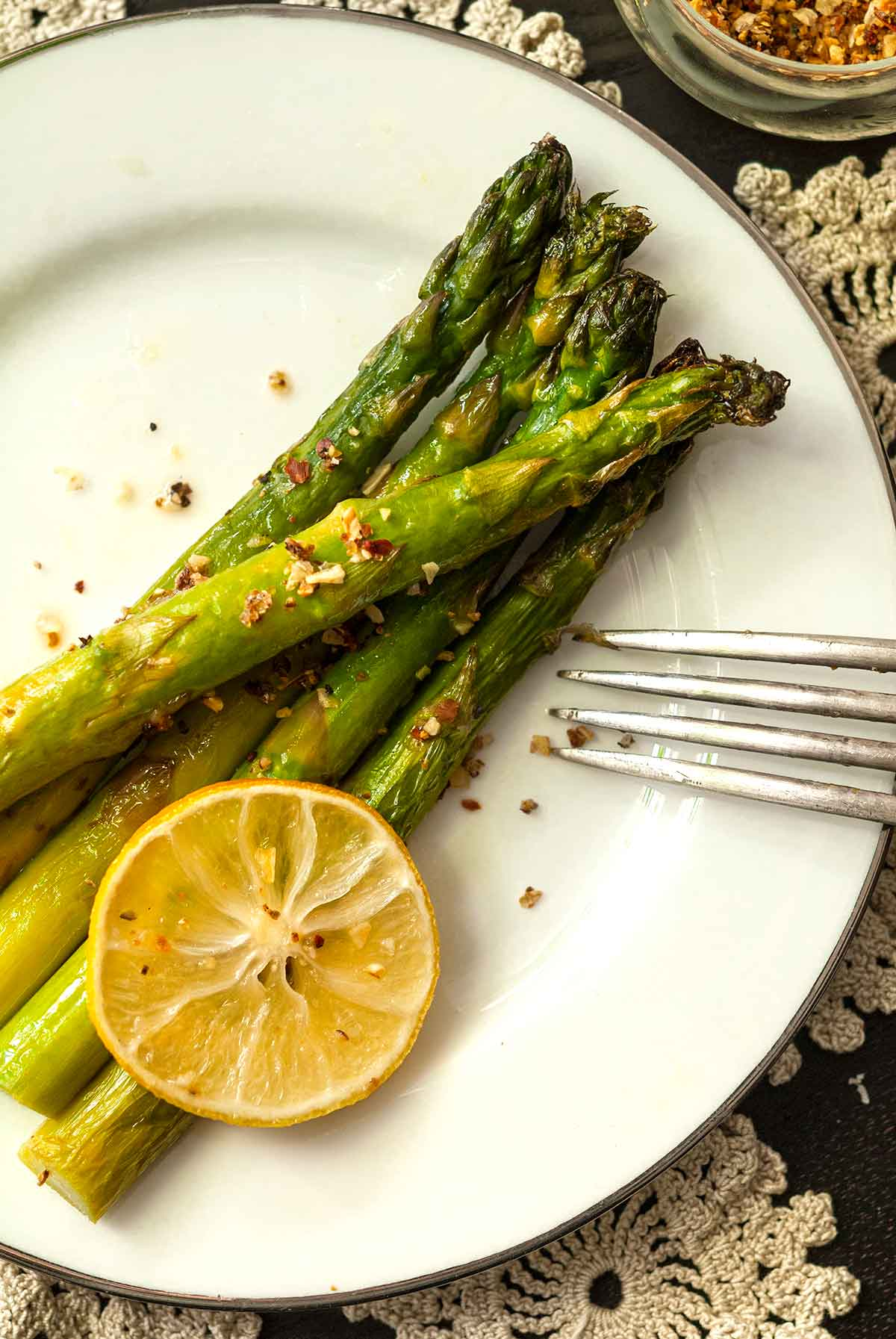 5 asparagus stalks on a plate with a fork, sprinkled with lemon pepper and garnished with a lemon slice.