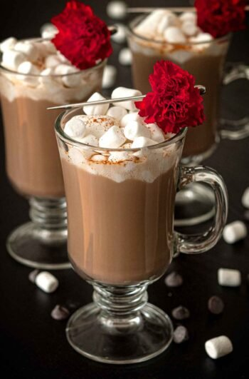 3 Hot chocolates, topped with marshmallows and flower garnishes on a table, sprinkled with marshmallows and chocolate chips.