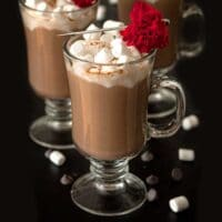 Hot chocolate, topped with marshmallows and a flower garnish on a table, sprinkled with marshmallows and chocolate chips.