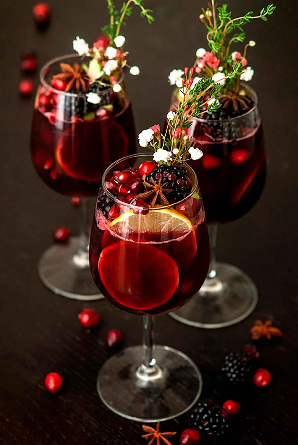 3 glasses of sangria garnished with fruits, flowers, herbs and star anise, with a few scattered cranberries and blackberries.