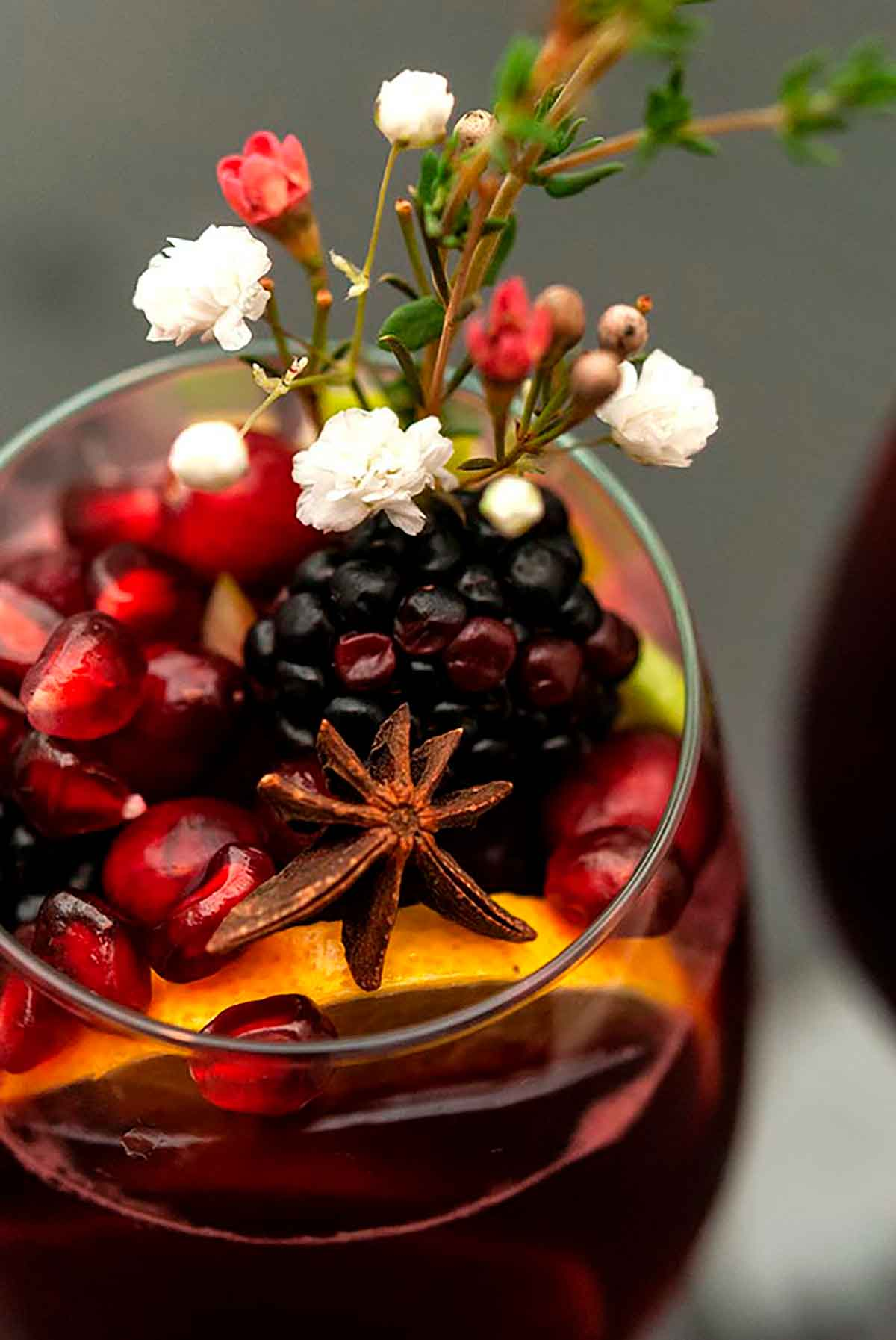 A glass of sangria garnished with fruits, flowers, herbs and star anise on a dark table.