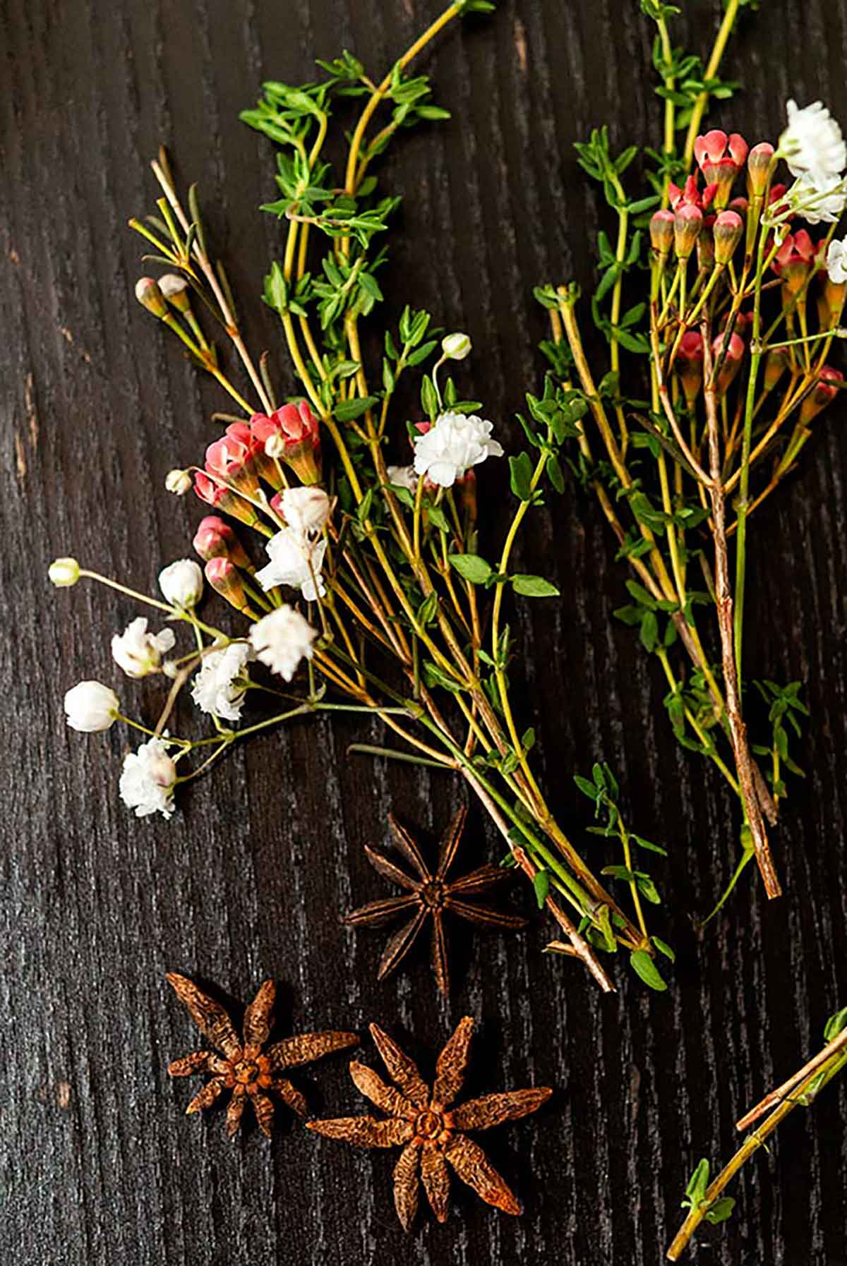 2 small bunches of herbs and flowers on a table with 3 star anise.