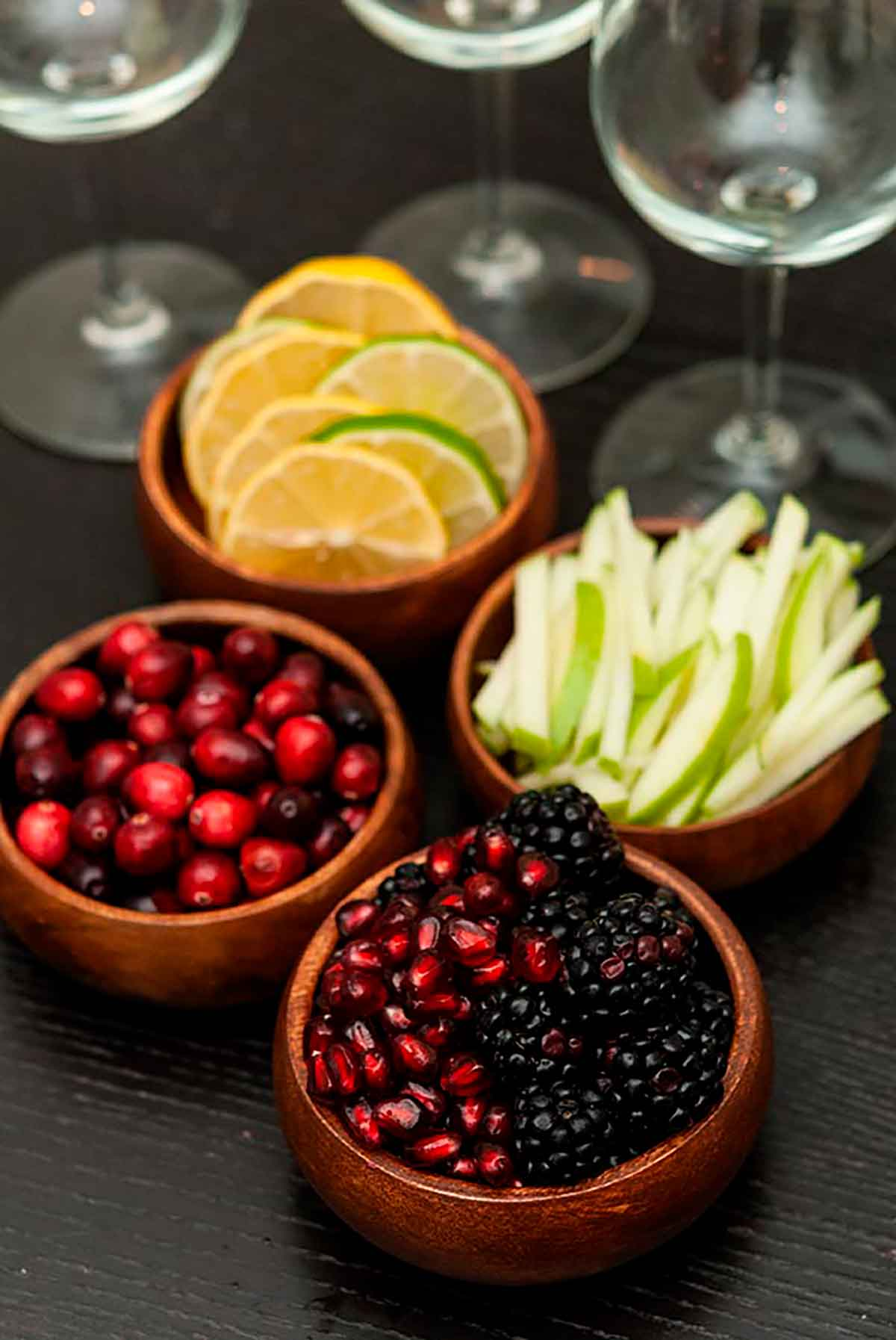 Berries, citrus and apple garnishes in small wooden bowls on a table with 3 empty wine glasses.