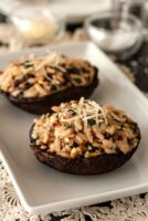 2 risotto-stuffed portobello mushrooms on a plate, garnished with a little fresh parmesan.