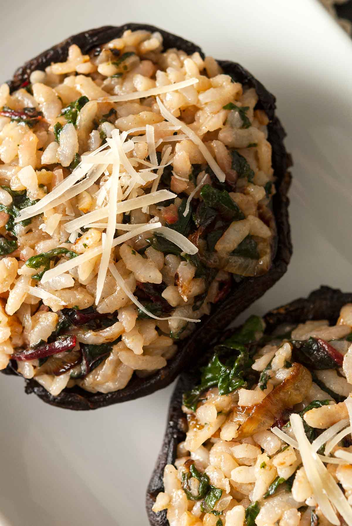 2 risotto-stuffed portobello mushrooms on a plate.