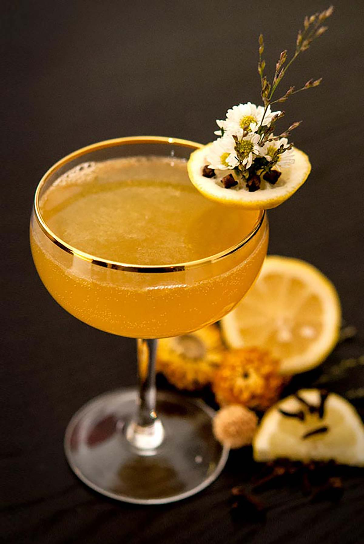 A cocktail garnished with daisies, lemon and cloves, sitting on a black table with sliced lemons and dry flowers around it.