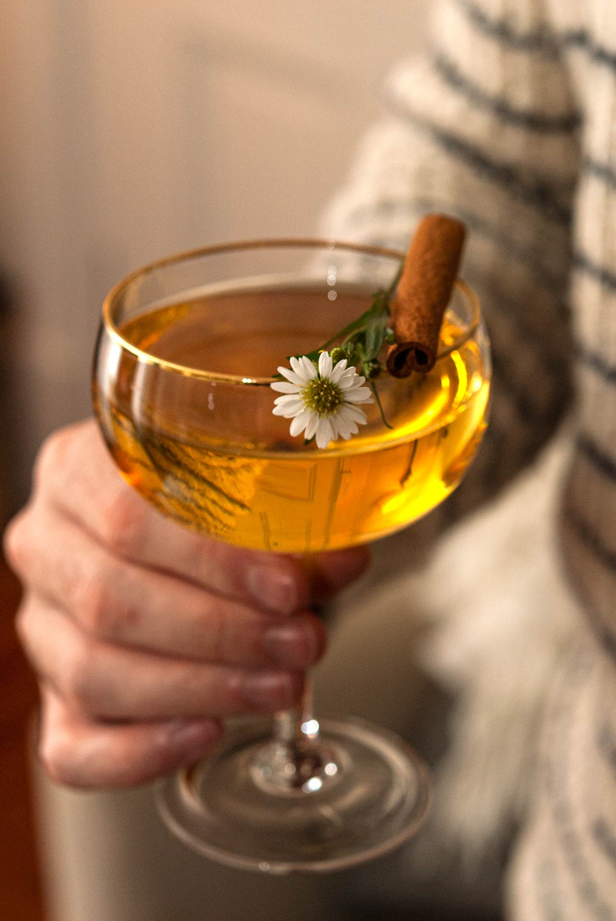 A man's hand holding a cocktail garnished with a daisy and cinnamon stick.