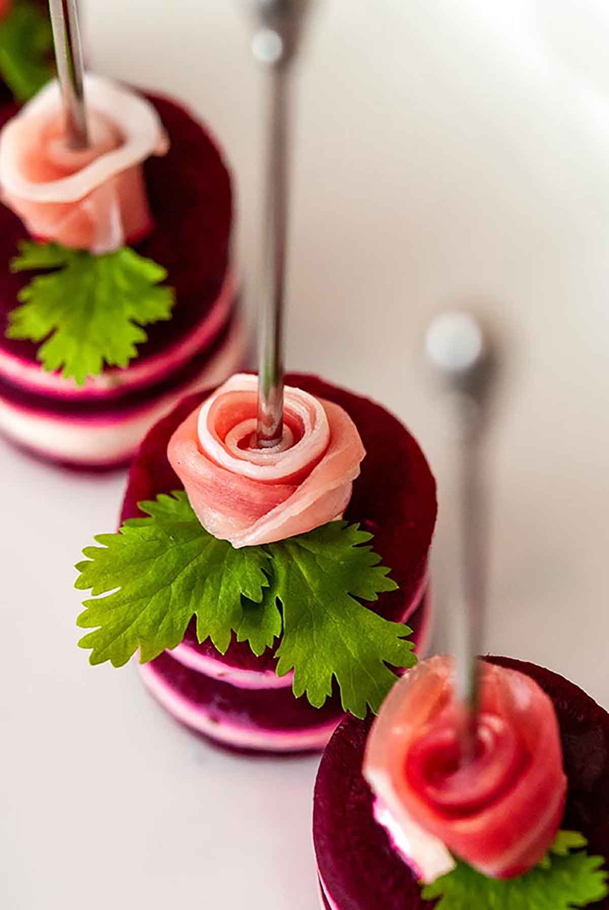 3 small beet napoleons, with a prosciutto rose and cilantro leaf on top, with cocktail pins through the center of the roses.