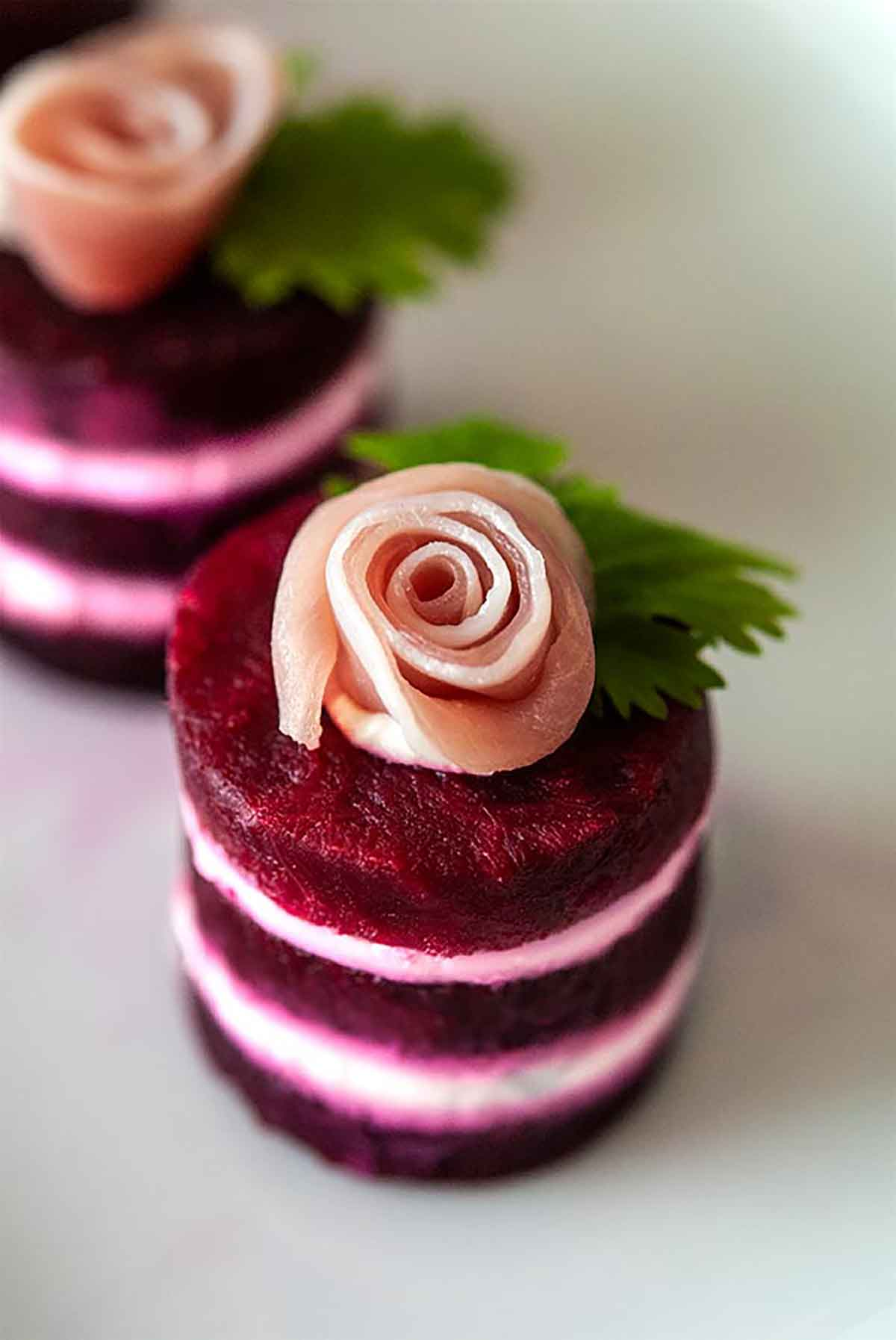 A small beet napoleon, with a prosciutto rose on top, on a white plate.