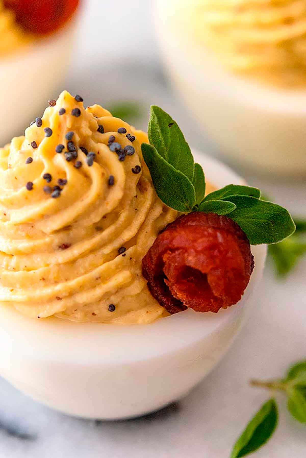 A deviled egg garnished with poppyseeds, a bacon rose, and small leaves on a white plate, surrounded by a few others.