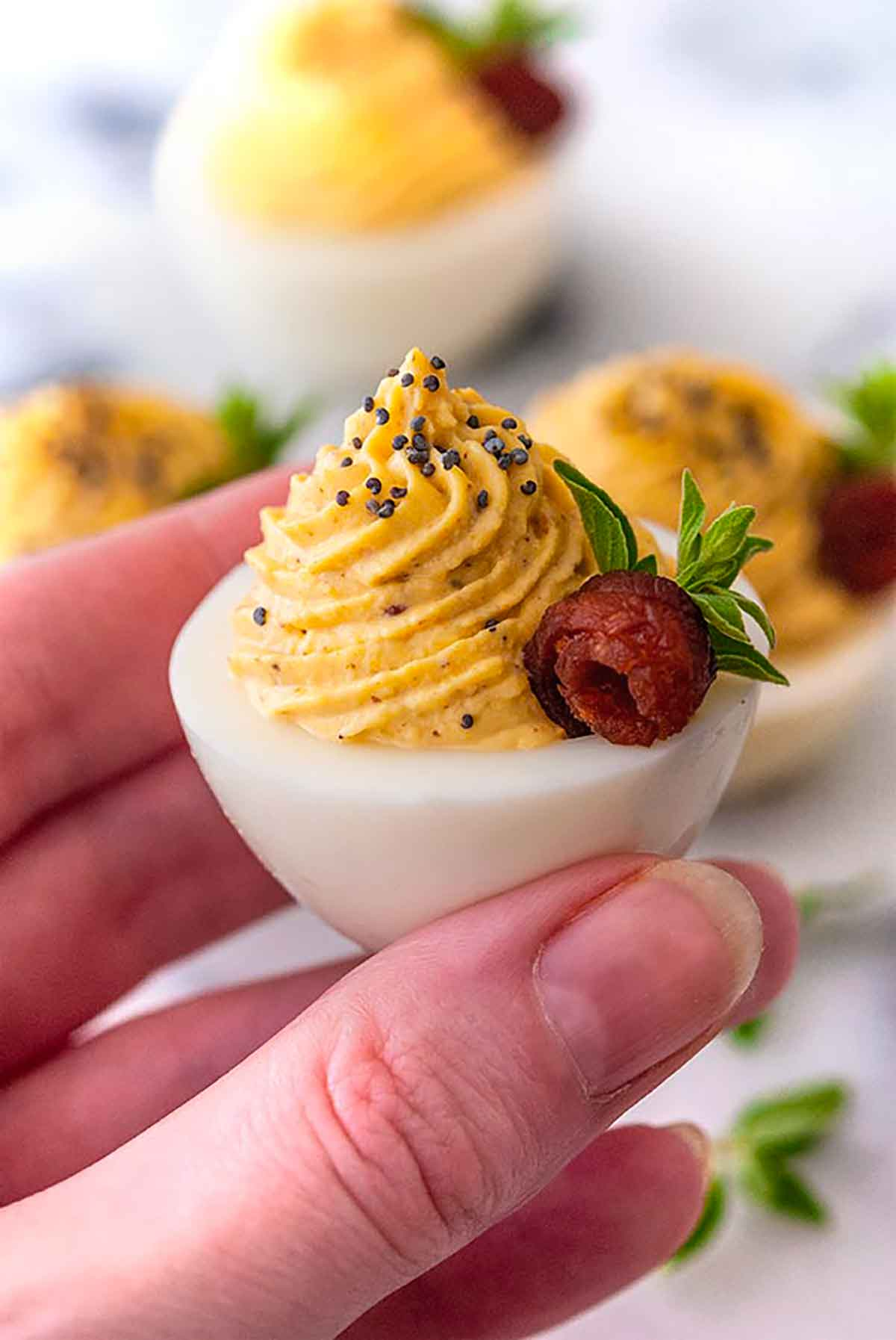 A hand holding a deviled egg, garnished with a bacon rose and oregano leaves.