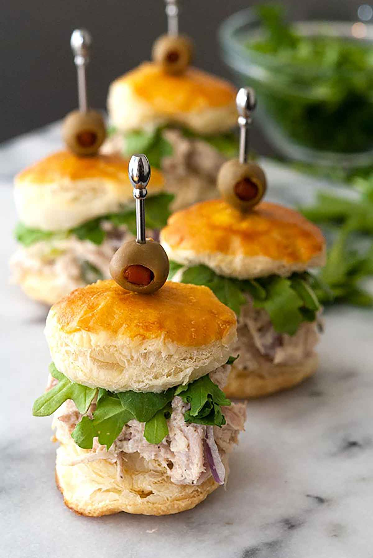 Chicken salad sliders on a marble board surrounded by arugula.