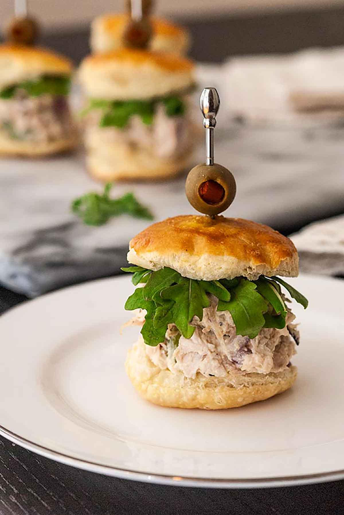 A chicken salad slider on a small plate with other sliders in the background.