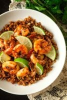 A bowl of lime shrimp atop coconut cauliflower rice on a lace tablecloth with cilantro beside it.