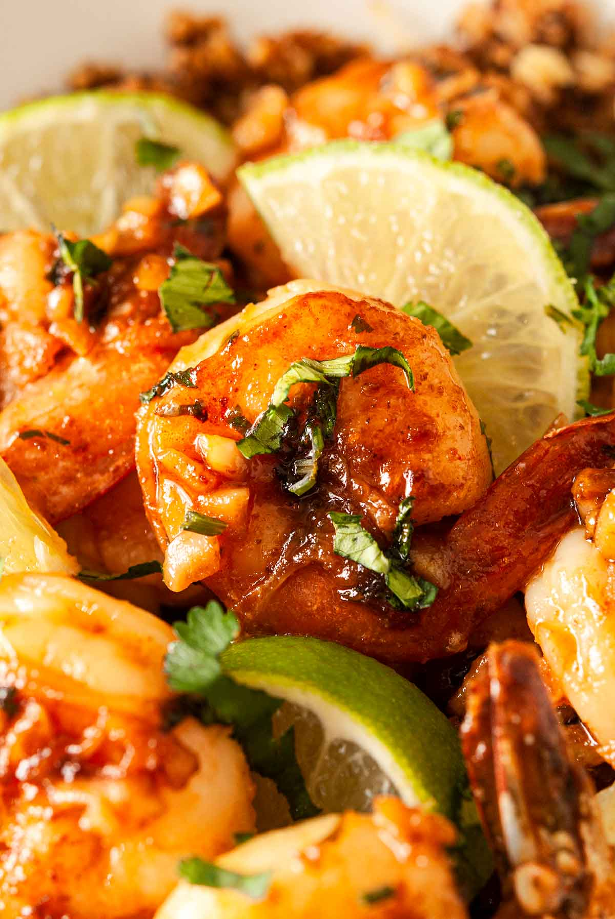 A honey lime shrimp in a bowl surrounded by lime slices and other cooked shrimp.