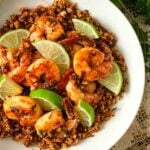 A bowl of lime shrimp atop coconut cauliflower rice on a lace tablecloth.