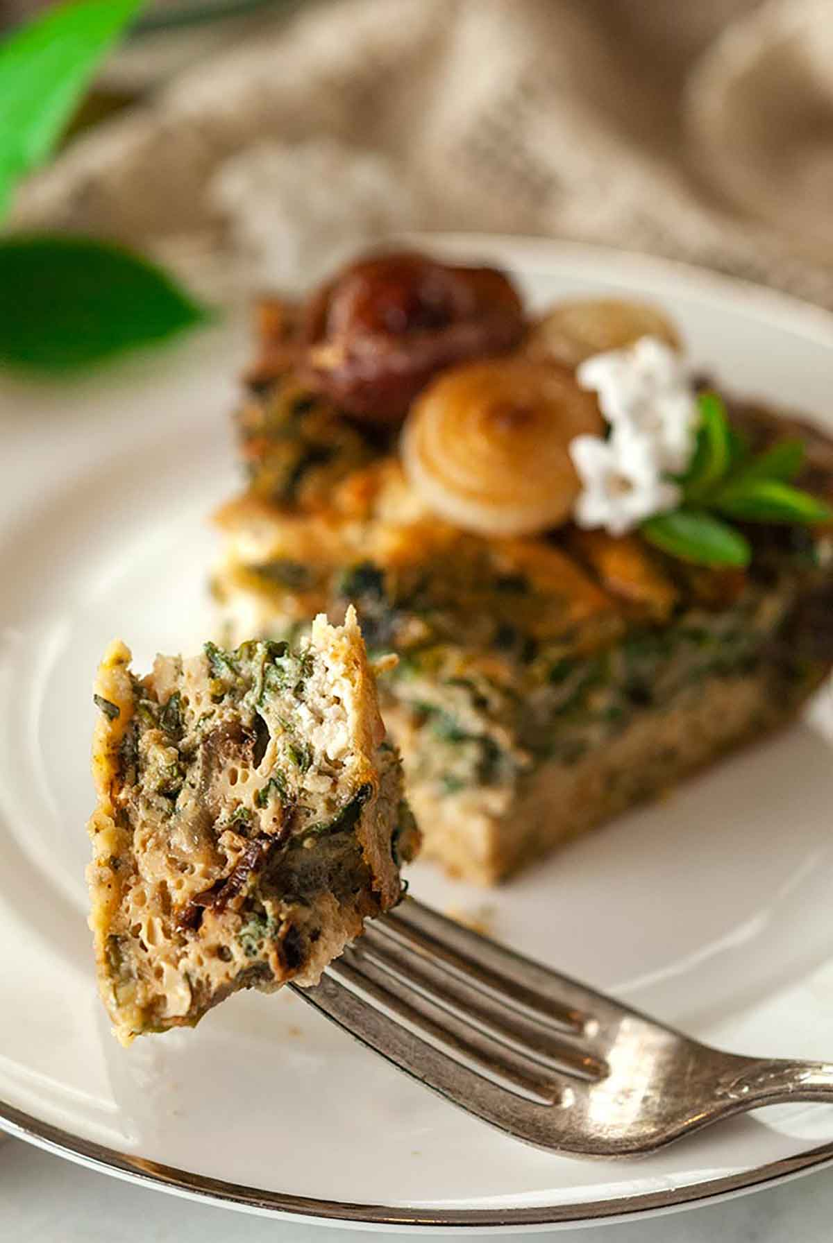 A piece of quiche on a fork with the slice in the background on a white plate.