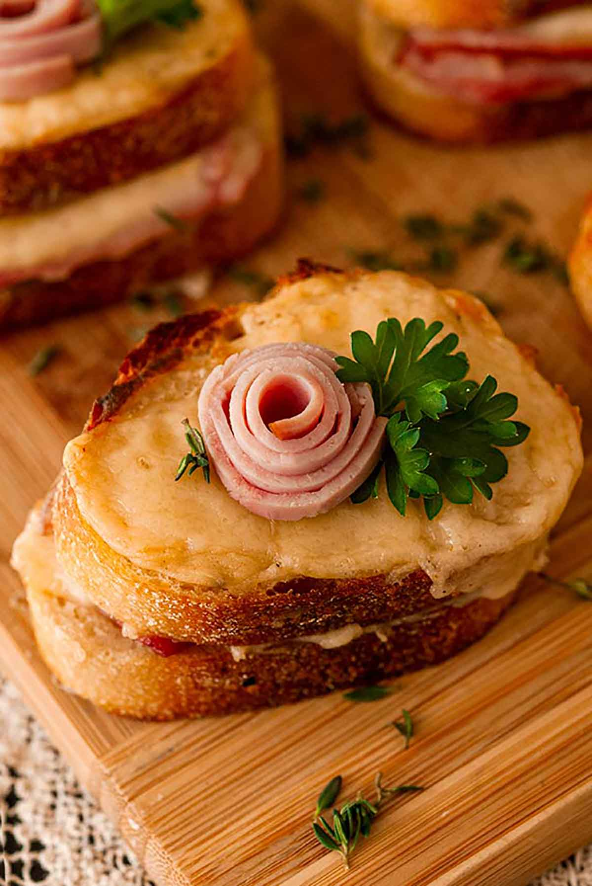 A mini croque monsieur with a small ham rose garnish and parsley on a decorative, antique plate.
