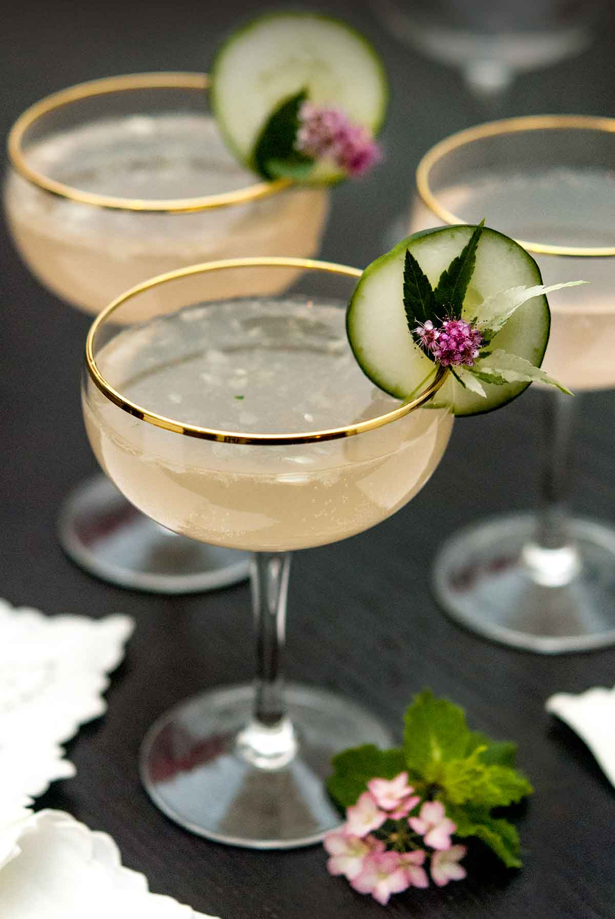 3 cocktails, garnished with a cucumber, leaf and small flowers with flowers at its base, as well as napkins.