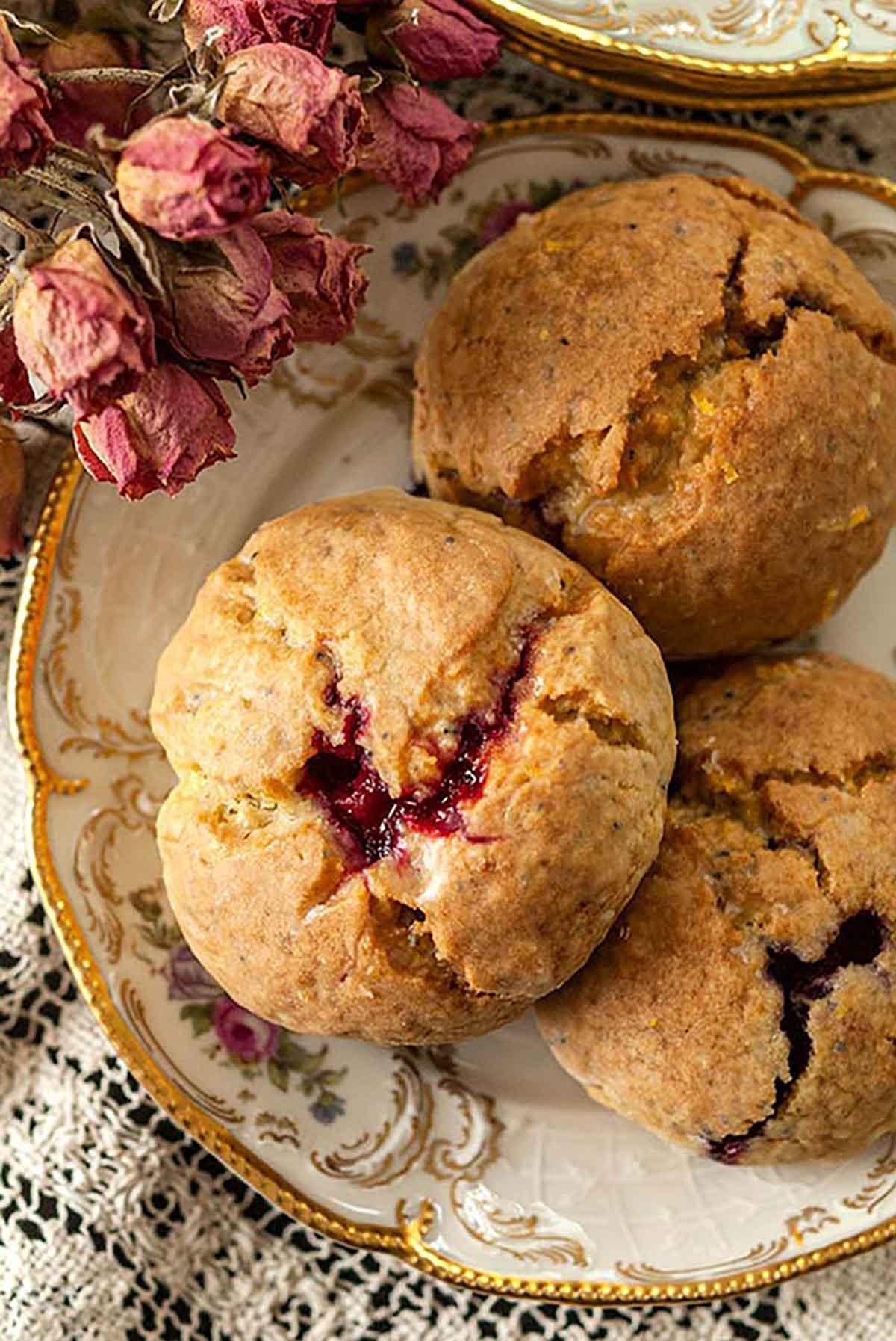 3 lemon-raspberry scones on an antique plate, beside a few dry, pink spray roses.