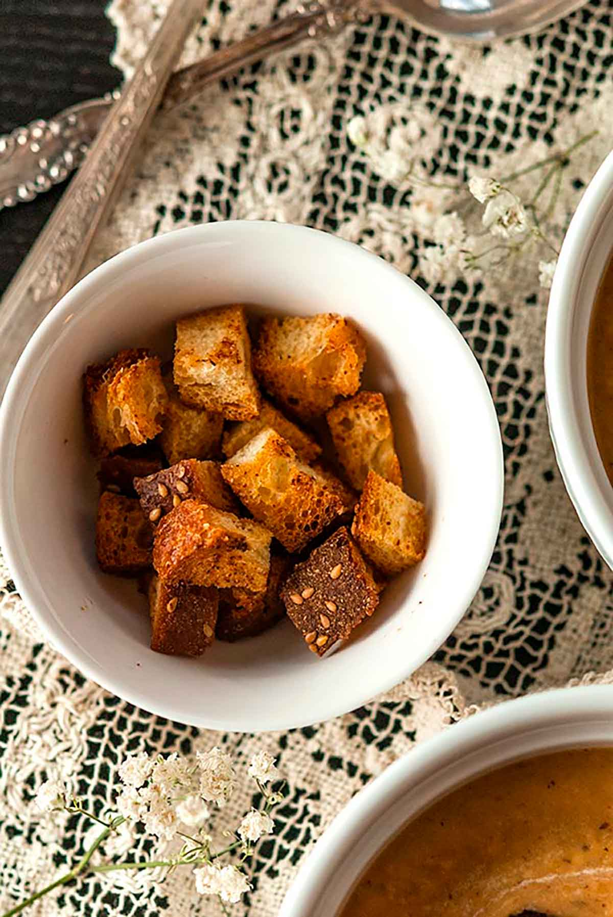 A small bowl of croutons on a lace table cloth.