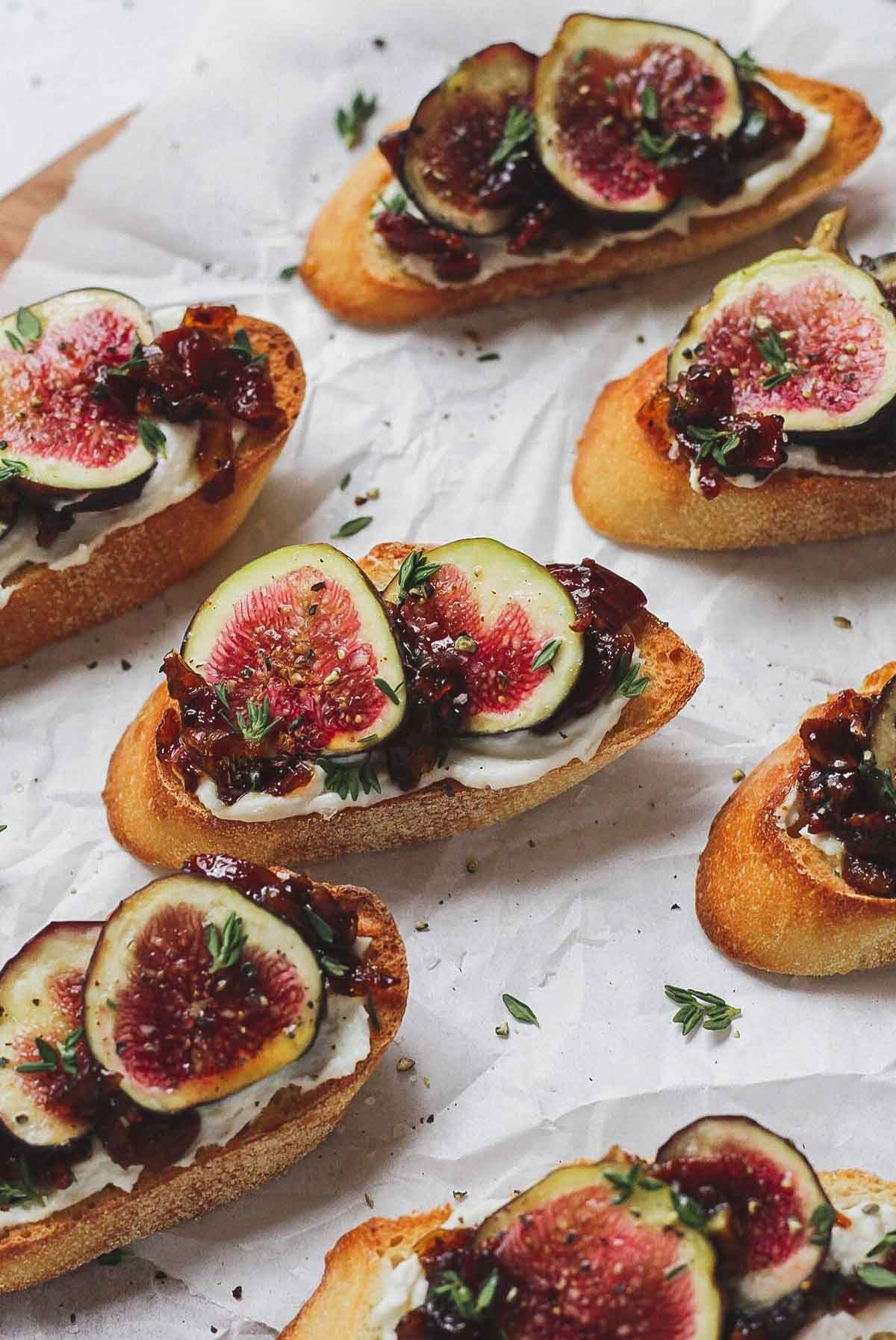 7 fig and bacon jam crostini on paper.