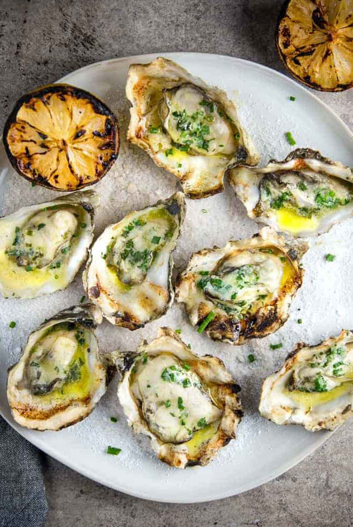 8 grilled oysters on a plate beside a grilled lemon slice.