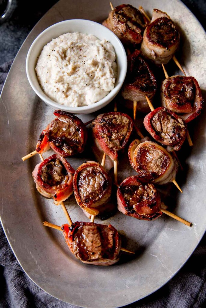 Filet mignon bites, wrapped in bacon and stuck with toothpicks, beside a sauce on a metal plate.
