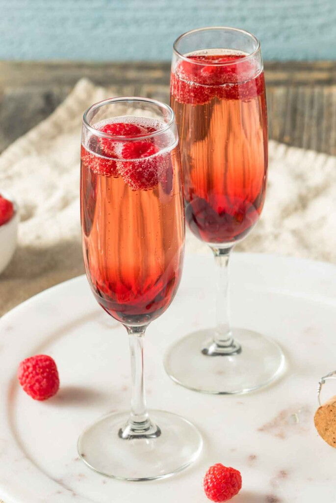 2 Kir Royale cocktails in champagne flutes on a table, garnished with raspberries.