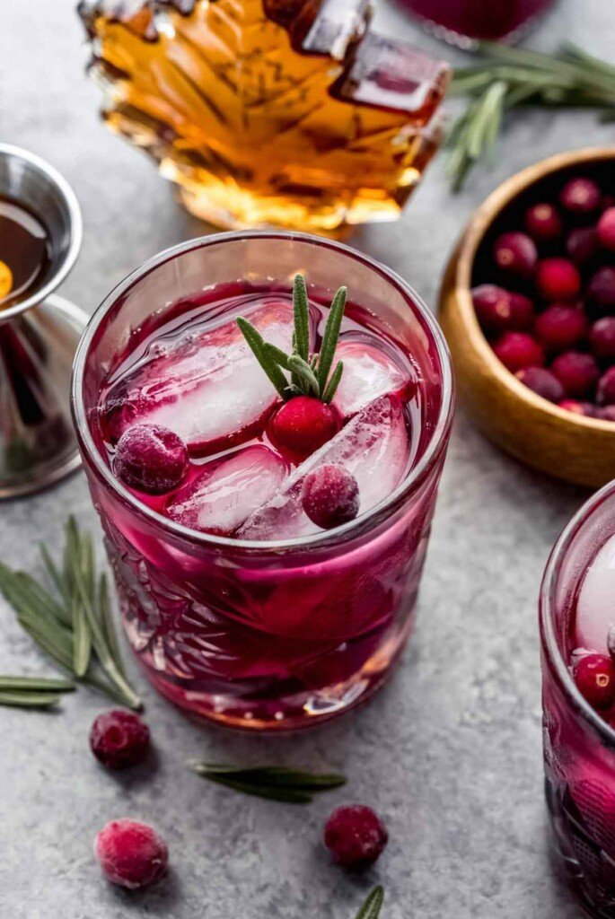 A maple cranberry smash cocktail on a table beside garnishes.
